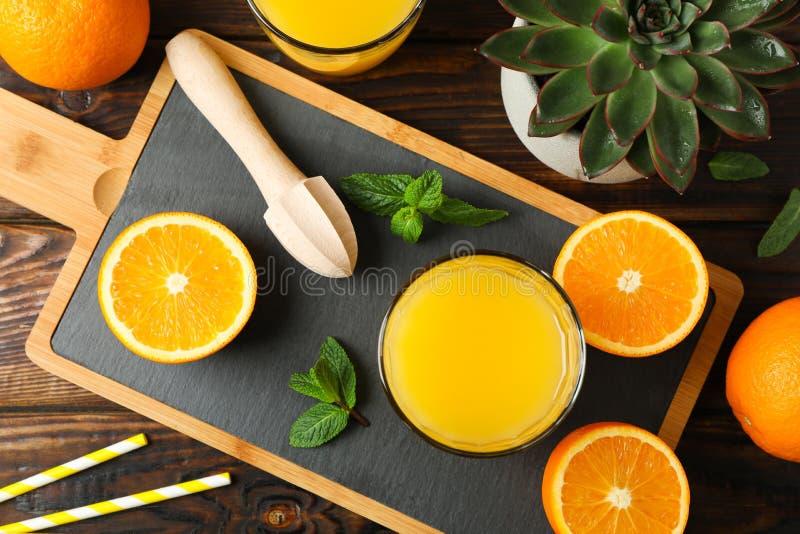 Tabla de cortar, zumo de naranja, juicer de madera, menta, naranja, t?bulo y planta suculenta en la tabla de madera, visi?n super fotografía de archivo
