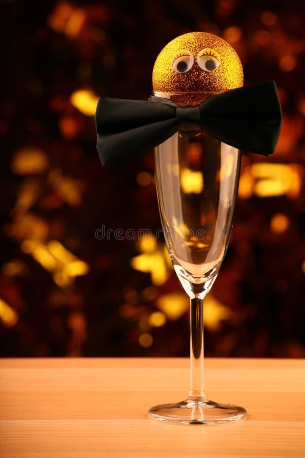 Tabla de cristal de la corbata de lazo del champán vacío plástico de los ojos de la bola del juguete del oro del Año Nuevo foto de archivo libre de regalías