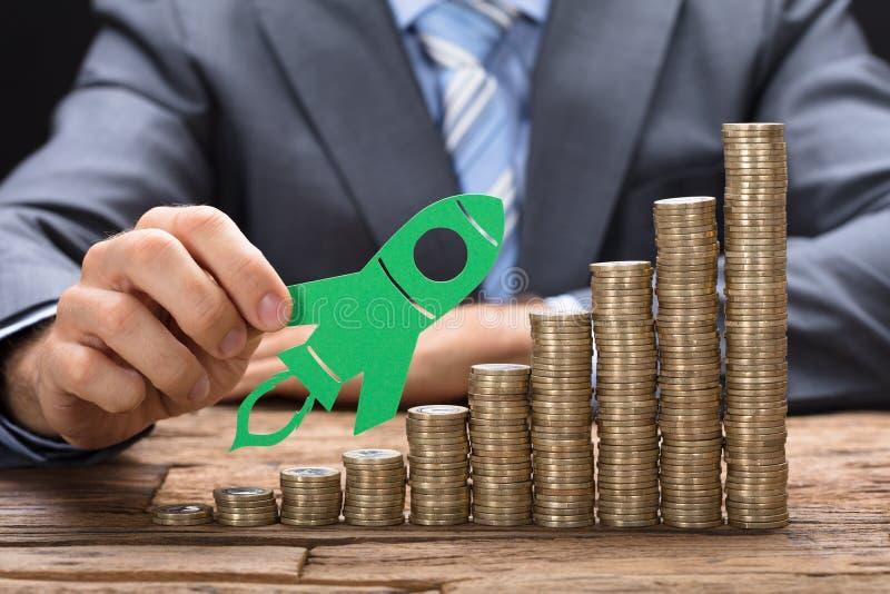 Tabla de Holding Green Paper Rocket On Stacked Coins On del hombre de negocios imagen de archivo