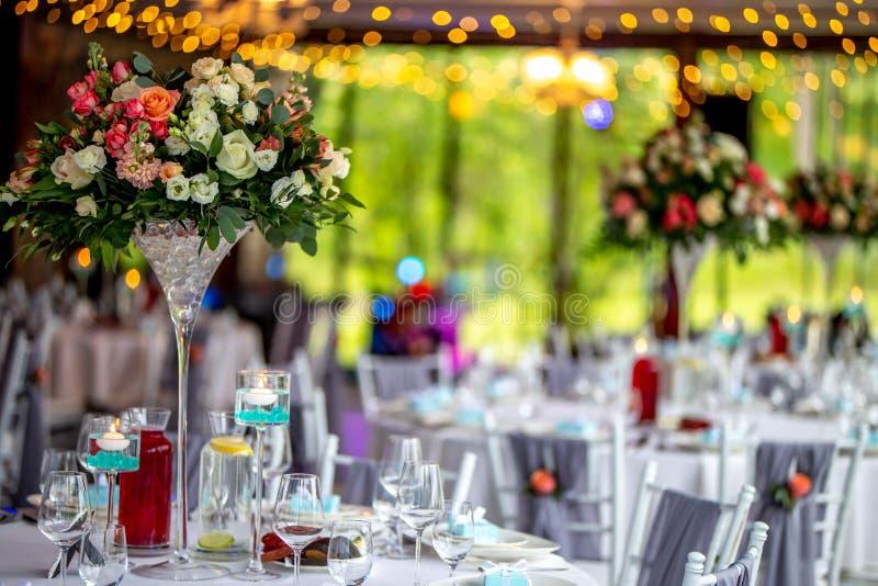 Tabla de la boda adornada con las flores y los platos imagen de archivo libre de regalías