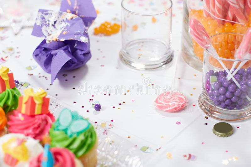 Tabla de la fiesta de cumpleaños de los niños con las magdalenas y el caramelo fotografía de archivo libre de regalías