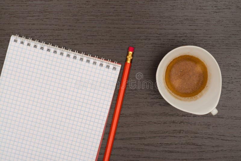 Tabla de la oficina con el cuaderno, el lápiz y la taza de café imagenes de archivo