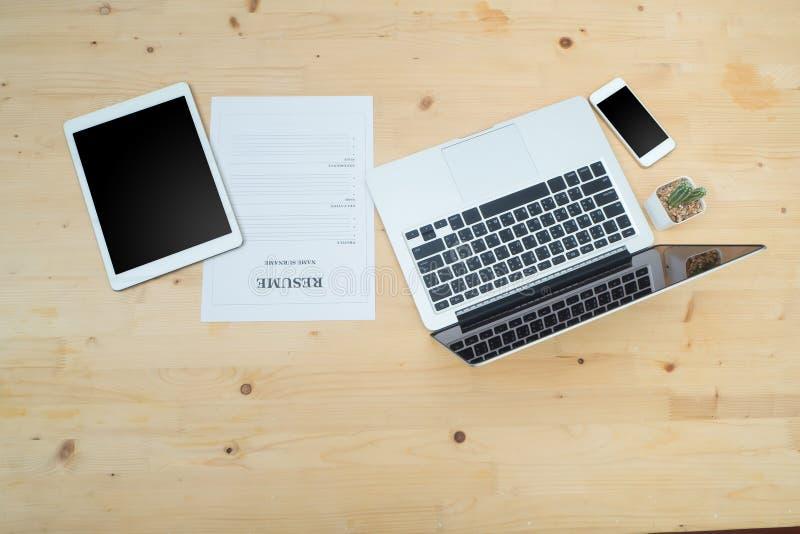 Tabla de la oficina con el informat del ordenador portátil, de la tableta, del smartphone y del curriculum vitae imagen de archivo