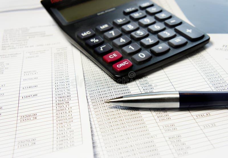 Tabla de la oficina con la calculadora, la pluma y el documento de contabilidad foto de archivo libre de regalías