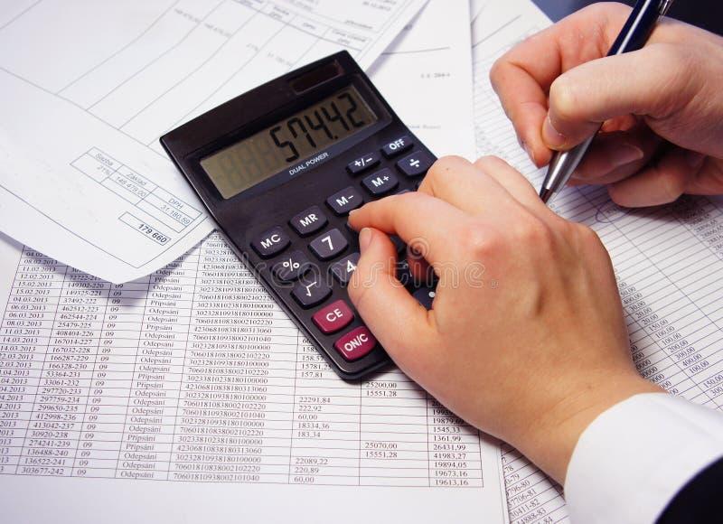 Tabla de la oficina con la calculadora, la pluma y el documento de contabilidad imagen de archivo