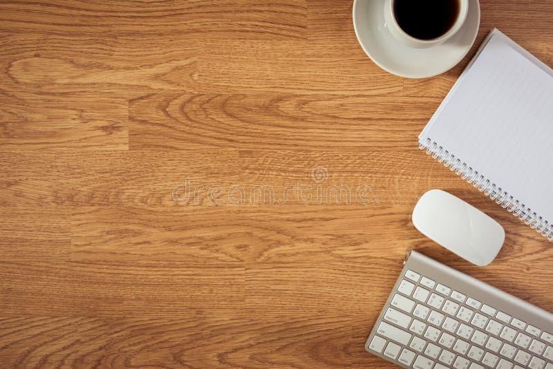 Tabla de la oficina con la libreta, ordenador y taza y ordenador de café fotos de archivo libres de regalías
