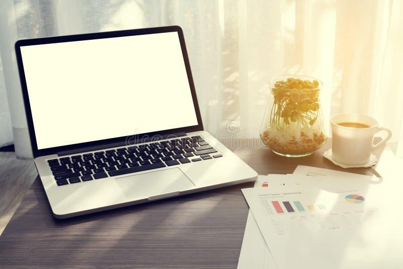 Tabla de la oficina con la pantalla en blanco en el ordenador portátil, taza de café, jardín imagen de archivo libre de regalías