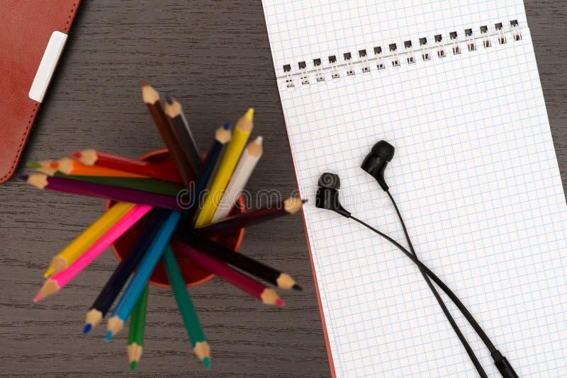 Tabla de la oficina con la tableta, los auriculares, los lápices y el cuaderno imagenes de archivo