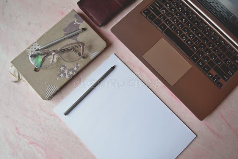Tabla de la oficina con laptpo, el cuaderno, la pluma, el lápiz, los vidrios, la cartera y el Libro Blanco imágenes de archivo libres de regalías