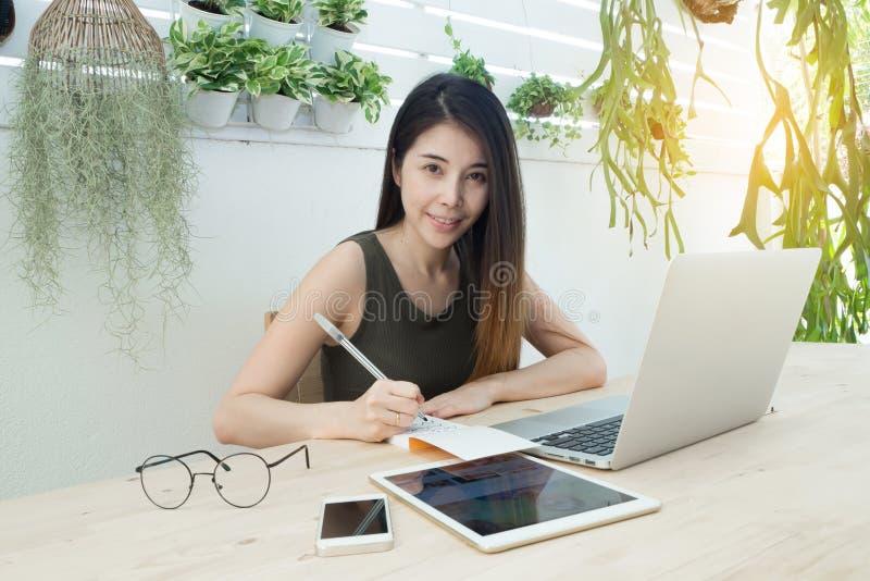 Tabla de la oficina con las mujeres jovenes en cara sonriente y la escritura encendido no fotografía de archivo libre de regalías