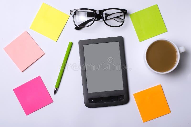 Tabla de la oficina con los accesorios: una tableta, vidrios, pluma, papel imagenes de archivo