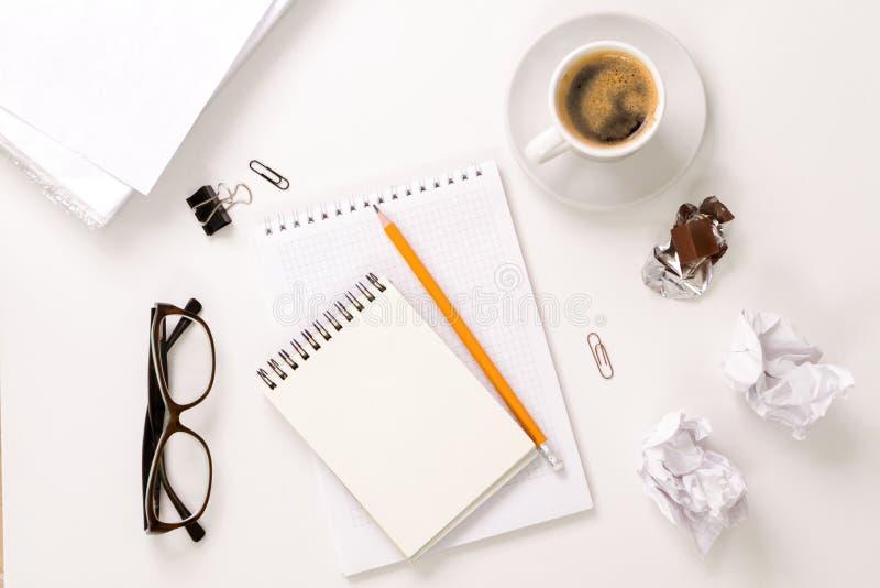 Tabla de la oficina con la taza de la libreta y de café Visión desde arriba con el espacio de la copia foto de archivo