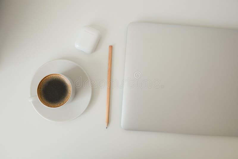 Tabla de la oficina en qué ordenador portátil, el café, la tableta, la cámara y otros artículos foto de archivo libre de regalías