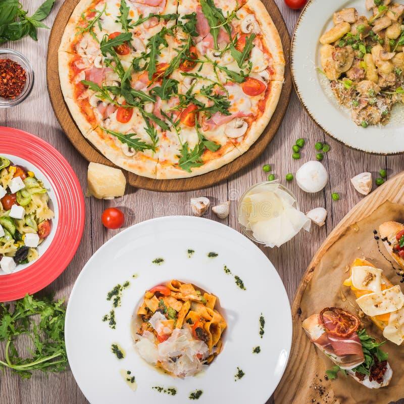 Tabla de la porción para el almuerzo de la pizza, pastas, bruschetta foto de archivo libre de regalías