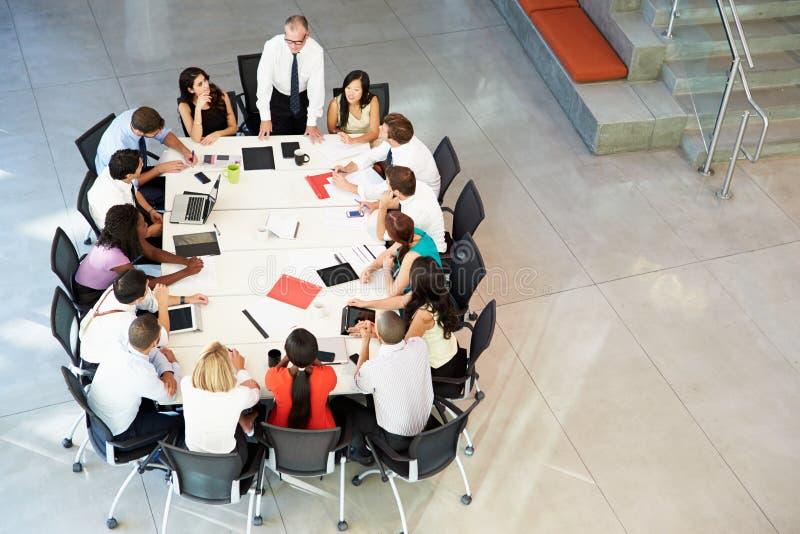 Tabla de la sala de reunión de Addressing Meeting Around del hombre de negocios foto de archivo