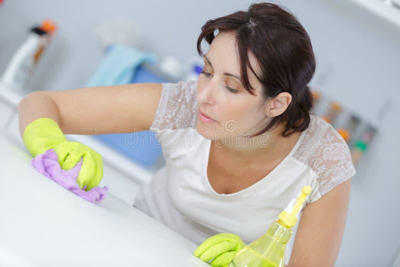 Tabla de la superficie de la limpieza del ama de casa con el desinfectante foto de archivo