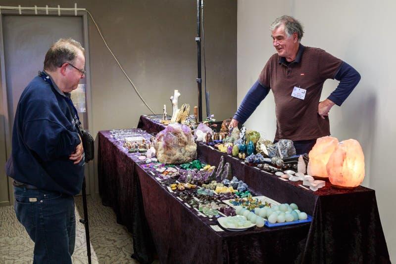 Tabla de las ventas cubierta en las gemas, cristales, y minerales, con un vendedor y un cliente fotos de archivo libres de regalías