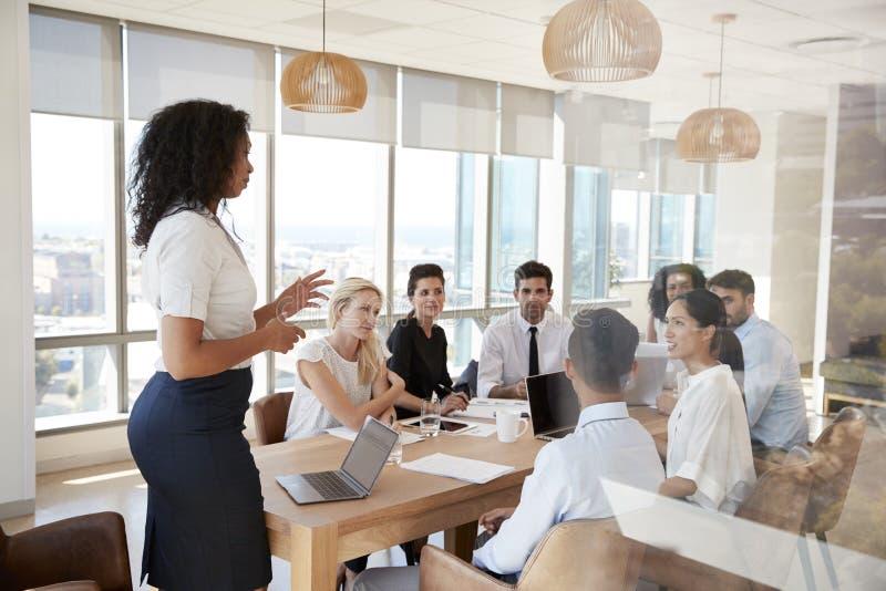 Tabla de Leads Meeting Around de la empresaria tirada a través de puerta foto de archivo libre de regalías