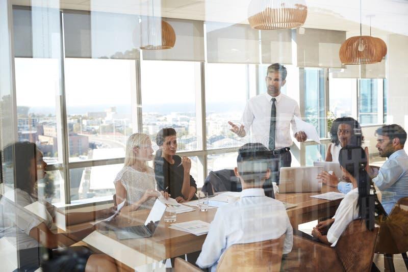 Tabla de Leads Meeting Around del hombre de negocios tirada a través de puerta imagen de archivo libre de regalías
