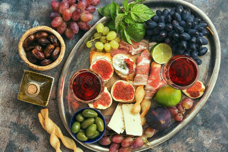 Tabla de los aperitivos con bocados y vino italianos de los antipasti en vidrios en una bandeja del metal Grissini tradicional de imagen de archivo
