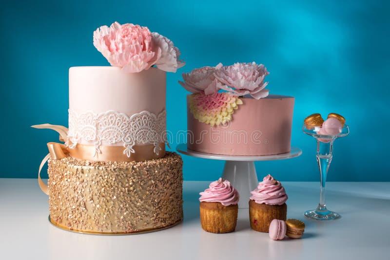 Tabla de lujo de la boda con una torta rosada hermosa adornada con la rosa y el oro del rosa de la masilla en un fondo azul imagen de archivo