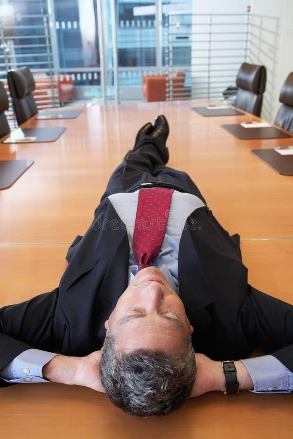Tabla de Lying On Conference del hombre de negocios foto de archivo