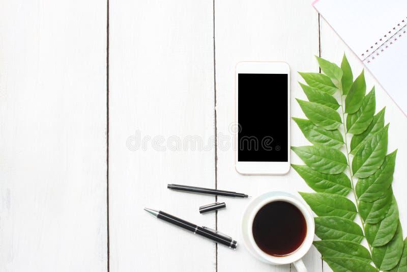 Tabla de madera blanca del escritorio de la visión superior con las fuentes del smartphone y el co fotos de archivo