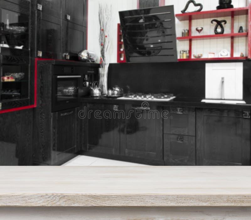 Tabla de madera blanqueada en fondo negro defocused del interior de la cocina imagenes de archivo
