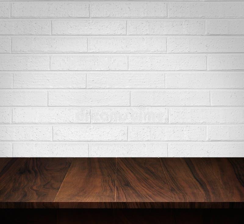 Tabla de madera con el fondo blanco de la pared de ladrillo imagen de archivo