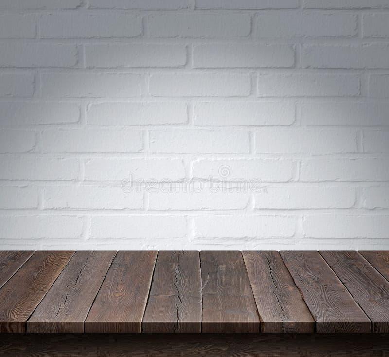 Tabla de madera con el fondo blanco de la pared de ladrillo foto de archivo libre de regalías