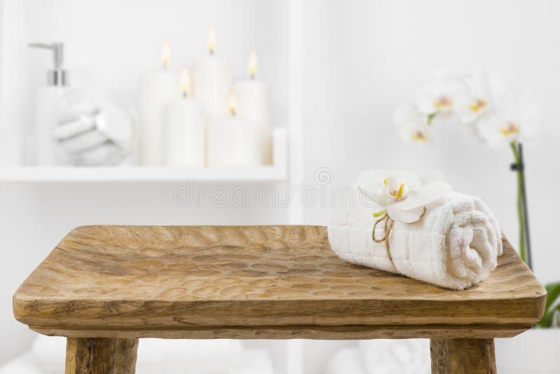 Tabla de madera con la toalla del balneario en fondo borroso del estante del cuarto de baño imagenes de archivo