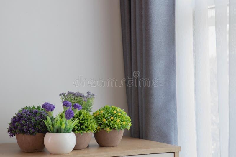 Tabla de madera con las flores de la decoración en el fondo blanco de la textura de la ventana de la cortina fotos de archivo libres de regalías
