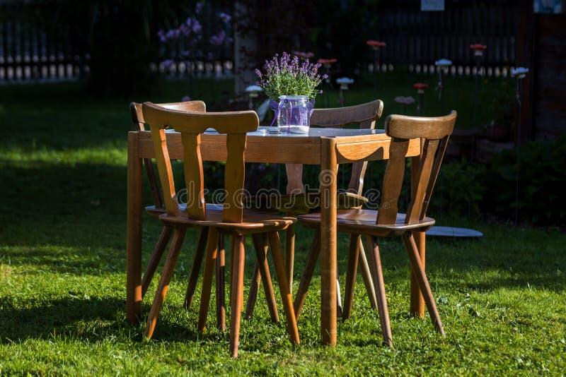 Tabla de madera con las sillas en el jardín foto de archivo