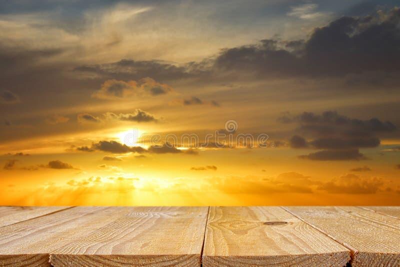 tabla de madera del tablero delante de la puesta del sol de oro fondo de exhibición del producto imagen de archivo