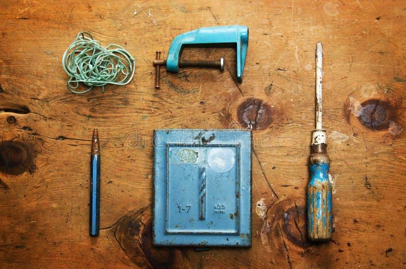 Tabla de madera del vintage con el taladro, el destornillador, la abrazadera, la plomada y la cuerda imagen de archivo