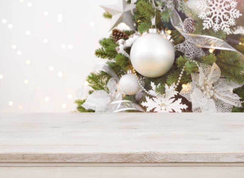 Tabla de madera delante del fondo adornado borroso del árbol de navidad imagenes de archivo