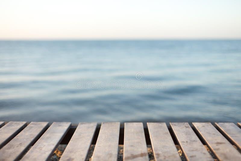 Tabla de madera delante del fondo borroso del mar foto de archivo