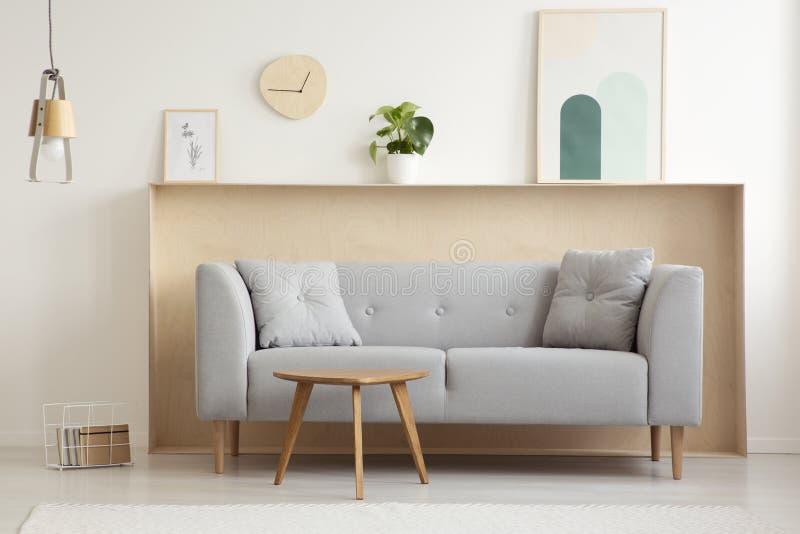Tabla de madera delante del sofá gris en interio simple de la sala de estar imagenes de archivo