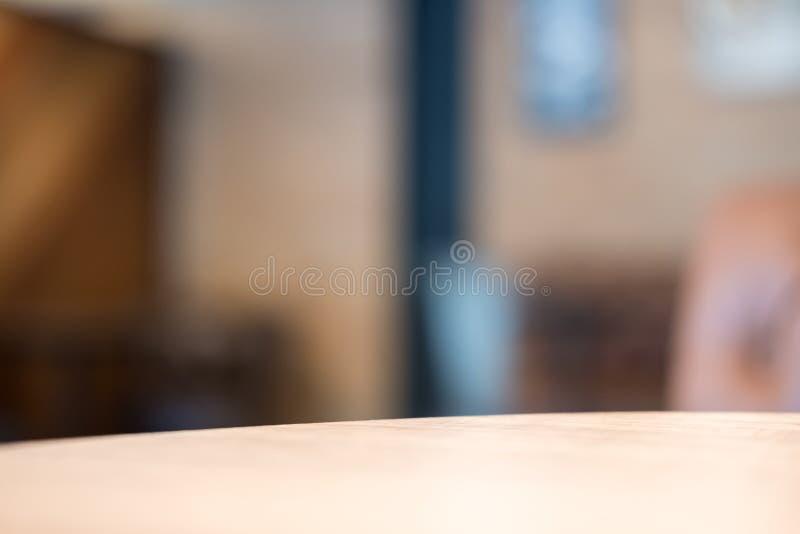 Tabla de madera en café con el fondo del extracto del bokeh de la falta de definición foto de archivo libre de regalías