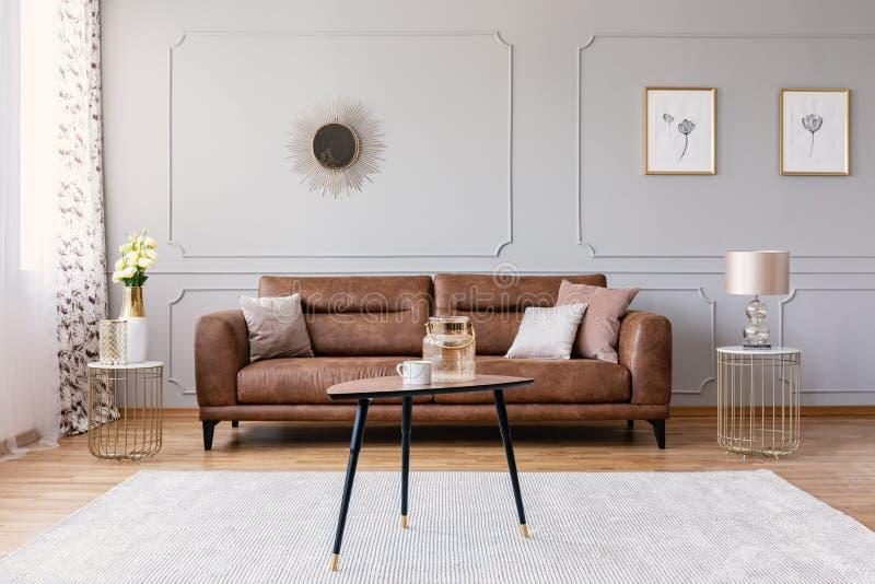 Tabla de madera en la alfombra delante del sofá de cuero en interior plano gris con los carteles y el espejo imágenes de archivo libres de regalías