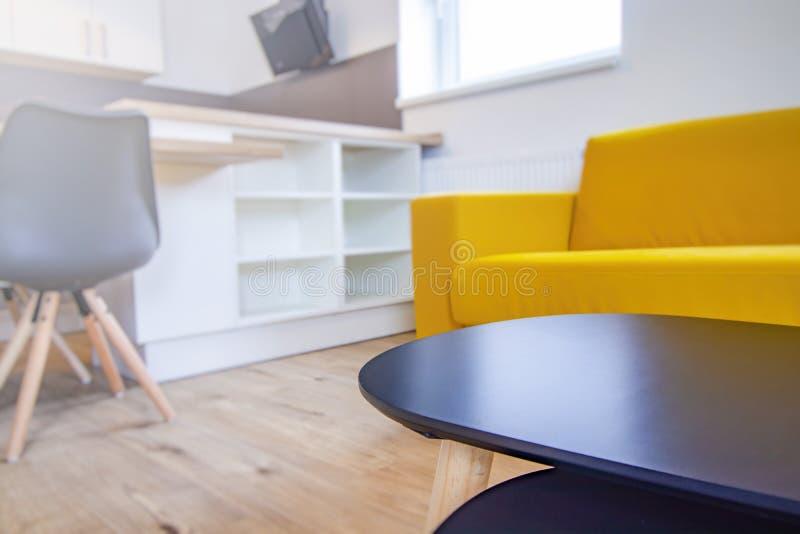 Tabla de madera en sala de estar Sofá amarillo, silla de madera y tabla blanca en fondo El fondo es falta de definición fotografía de archivo