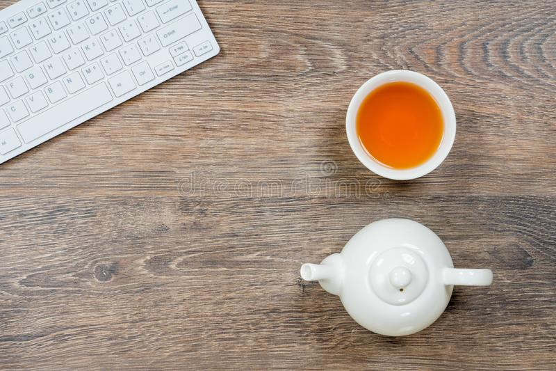 Tabla de madera gris de la oficina con el teclado y el té de ordenador imágenes de archivo libres de regalías