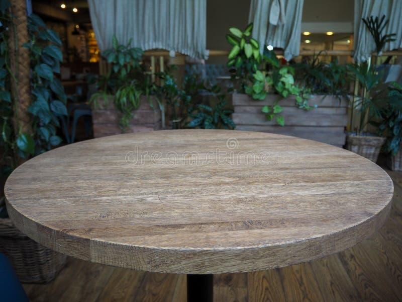 Tabla de madera de la ronda vacía en un restaurante en el fondo de plantas verdes fotos de archivo libres de regalías