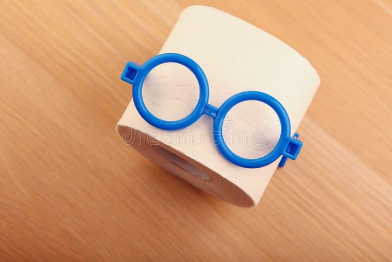 Tabla de madera de los vidrios plásticos azules del papel higiénico foto de archivo libre de regalías