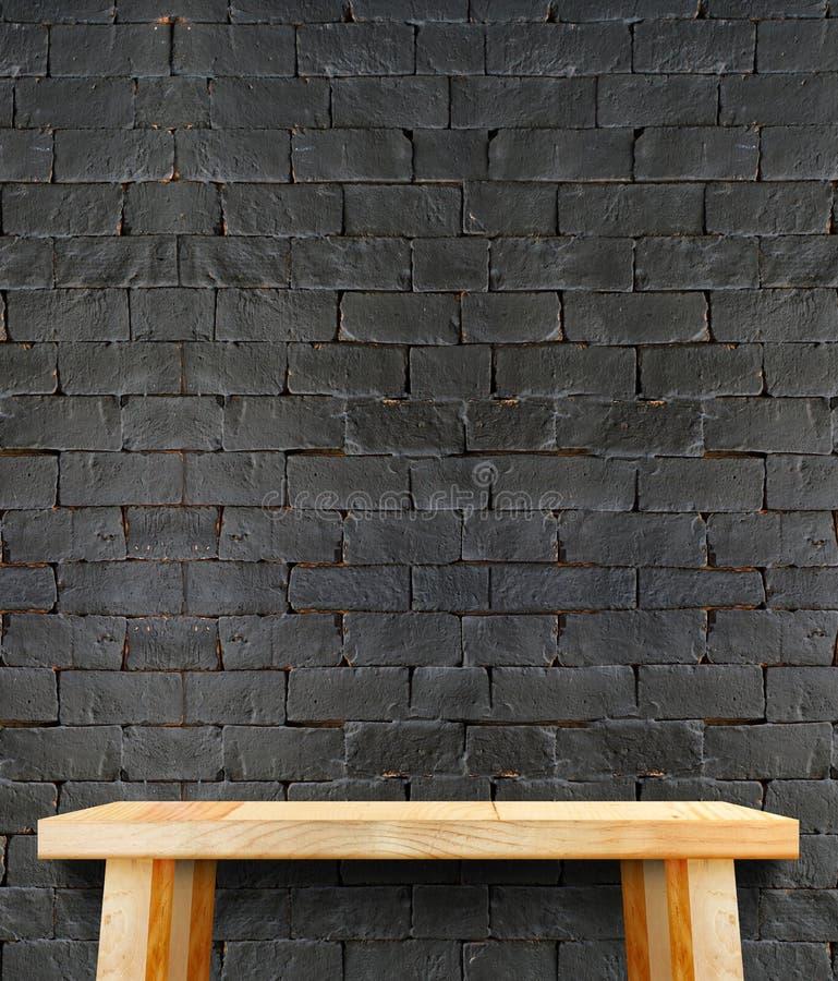Tabla de madera moderna en blanco con la pierna en la pared de ladrillo negra, plantilla fotografía de archivo libre de regalías