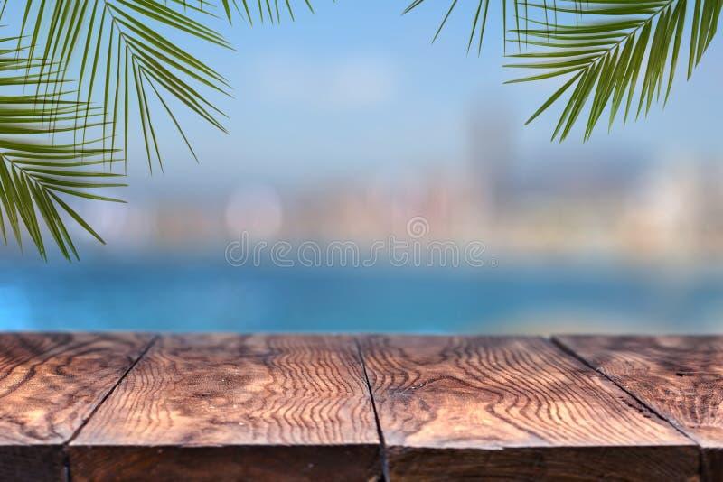 Tabla de madera o mofa de madera para arriba con las palmeras contra la perspectiva de una ciudad borrosa imágenes de archivo libres de regalías
