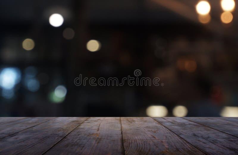 Tabla de madera oscura vacía delante del fondo borroso abstracto del interior del restaurante, del café y de la cafetería puede s fotos de archivo