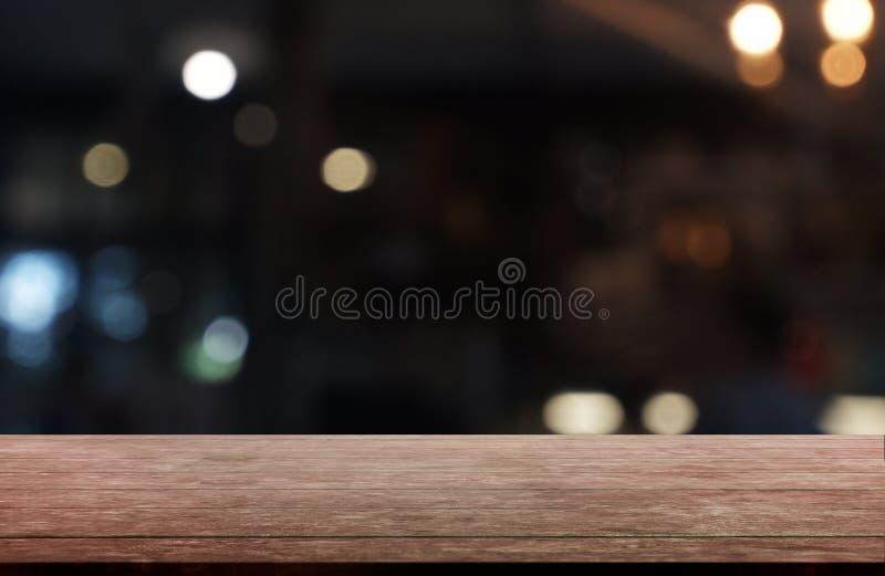 Tabla de madera oscura vacía delante del fondo borroso abstracto del interior del restaurante, del café y de la cafetería puede s foto de archivo libre de regalías