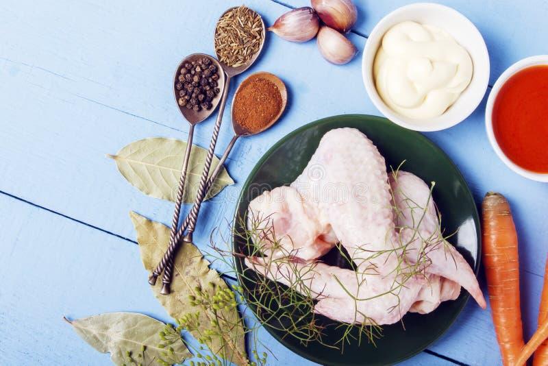 Tabla de madera rústica con los ingredientes frescos para la comida sana Alas de pollo crudas con las especias naturales para la  fotos de archivo