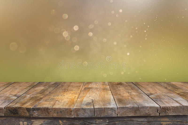 Tabla de madera rústica delante del verde del brillo y de luces brillantes del bokeh del oro fotografía de archivo